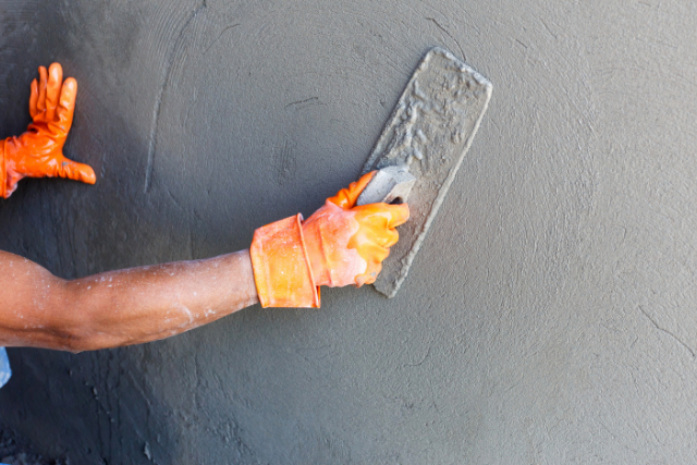 Concrete resurfacing wall by a worker with tool