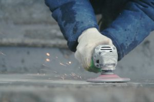 Resurfacing concrete wall by a worker with a power tool
